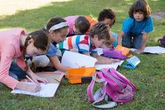 Παιδιά σχολείου που κάνουν την εργασία στη χλόη Στοκ Φωτογραφίες