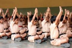 Παιδιά σχολείου που κάνουν τη γιόγκα με τους δασκάλους Στοκ Φωτογραφίες