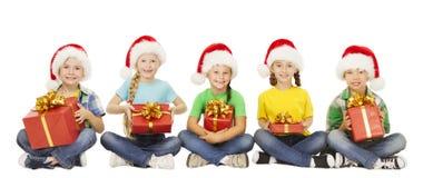 Παιδιά Χριστουγέννων, παρόν κιβώτιο δώρων, παιδιά στο καπέλο Santa Χριστουγέννων Στοκ φωτογραφία με δικαίωμα ελεύθερης χρήσης