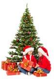 Παιδιά Χριστουγέννων στο καπέλο Santa κάτω από το χριστουγεννιάτικο δέντρο, ανοικτό παρόν κιβώτιο δώρων στοκ εικόνα με δικαίωμα ελεύθερης χρήσης
