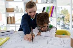 Παιδιά ως ανώτατα στελέχη επιχείρησης που σύρουν τις γραφικές παραστάσεις Στοκ Εικόνες