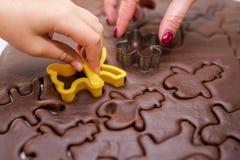 Παιδιά ` s και χέρι γυναικών ` s που κατασκευάζει τα μπισκότα μελοψωμάτων Χριστουγέννων στοκ φωτογραφίες με δικαίωμα ελεύθερης χρήσης