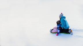 Παιδιά Sledding κάτω από το Hill χιονιού στη γρήγορη ταχύτητα ελκήθρων στοκ εικόνα με δικαίωμα ελεύθερης χρήσης