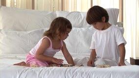 Παιδιά Wellbehaved που παίζουν στο κρεβάτι απόθεμα βίντεο