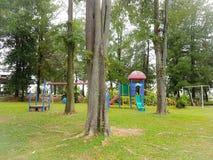 Παιδική χαρά των ζωηρόχρωμων παιδιών με τα πολύβλαστες δέντρα και τη χλόη Στοκ Φωτογραφίες