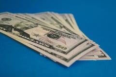 Πακέτο των τραπεζογραμματίων πενήντα δολαρίων που απομονώνονται στο μπλε υπόβαθρο στοκ φωτογραφία