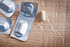 Πακέτο φουσκαλών με τα χάπια στον ξύλινο πίνακα ιατρικό Στοκ Εικόνες