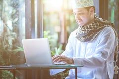 Πακιστανικό μουσουλμανικό άτομο που εργάζεται στο lap-top στον καφέ στοκ εικόνες με δικαίωμα ελεύθερης χρήσης