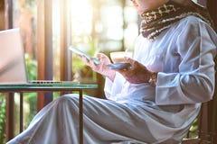 Πακιστανικό μουσουλμανικό άτομο χρησιμοποιώντας το κινητό τηλέφωνο και πίνοντας τον καφέ στον καφέ στοκ φωτογραφίες