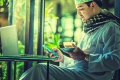 Πακιστανικό μουσουλμανικό άτομο χρησιμοποιώντας το κινητό τηλέφωνο και πίνοντας τον καφέ στον καφέ στοκ εικόνα