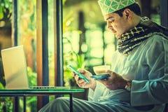Πακιστανικό μουσουλμανικό άτομο χρησιμοποιώντας το κινητό τηλέφωνο και πίνοντας τον καφέ στον καφέ στοκ φωτογραφίες με δικαίωμα ελεύθερης χρήσης