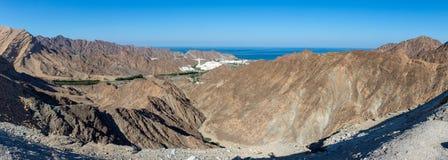 Παλάτι Al Bustan κοντά στην παλαιά πόλη, Muscat στο Ομάν που κοιτάζει κάτω από τα βουνά που φιλτράρουν πέρα από τη θεαματική σκην στοκ εικόνα
