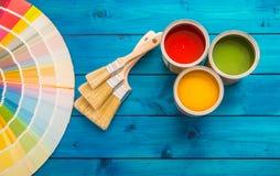 Παλέτα χρώματος δοχείων χρωμάτων, δοχεία που ανοίγουν με τις βούρτσες στον μπλε πίνακα στοκ εικόνα