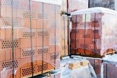 Παλέτες αποθεμάτων από κόκκινα τούβλα που τυλίγονται στην ταινία τεντωμάτων στο χονδρικό υπαίθριο κατάστημα αγοράς ot Εργοτάξιο ο στοκ εικόνες