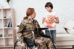 Παλαίμαχος γυναικών στην αναπηρική καρέκλα επιστρεφόμενο σπίτι Ο γιος είναι ευτυχής να δει τη μητέρα του μετά από να επιστρέψει α Στοκ Φωτογραφίες
