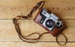 Παλαιά αναδρομική κάμερα στους εκλεκτής ποιότητας αγροτικούς ξύλινους πίνακες σανίδων Στοκ Φωτογραφία