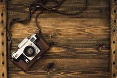 Παλαιά αναδρομική κάμερα στους εκλεκτής ποιότητας αγροτικούς ξύλινους πίνακες σανίδων Στοκ Εικόνα