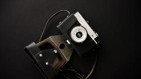 Παλαιά αναδρομική κάμερα ταινιών σε περίπτωση δέρματος στο μαύρο υπόβαθρο φιλμ μικρού μήκους