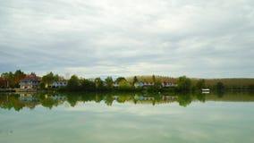 Παλαιά αντανάκλαση σπιτιών θερέτρου στο νερό λιμνών, φρεσκάδα φιλμ μικρού μήκους