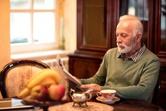 Παλαιά ανώτερη συνεδρίαση ατόμων στο σπίτι μόνο και ανάγνωση μια εφημερίδα Στοκ Εικόνες