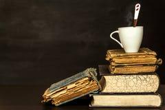 Παλαιά βιβλία και ένα φλυτζάνι πορσελάνης Μελέτες λογοτεχνίας Χαλάρωση με ένα βιβλίο ποτό ζεστό Στοκ εικόνα με δικαίωμα ελεύθερης χρήσης
