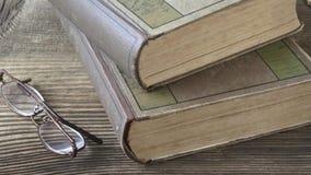 Παλαιά βιβλία με τα γυαλιά ανάγνωσης σε έναν ξύλινο πίνακα απόθεμα βίντεο
