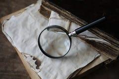 Παλαιά βιβλία σε έναν ξύλινο πίνακα και πιό magnifier Στοκ Φωτογραφία