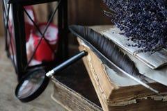 Παλαιά βιβλία σε έναν ξύλινο πίνακα και πιό magnifier Στοκ φωτογραφία με δικαίωμα ελεύθερης χρήσης
