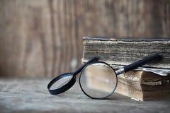 Παλαιά βιβλία σε έναν ξύλινο πίνακα και πιό magnifier Στοκ Εικόνα