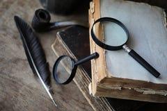 Παλαιά βιβλία σε έναν ξύλινο πίνακα και πιό magnifier Στοκ φωτογραφίες με δικαίωμα ελεύθερης χρήσης