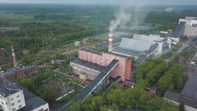 Παλαιά βιομηχανικά κτήρια τούβλου με τον ψηλό σωρό καπνοδόχων που περιβάλλεται από τη δασική εναέρια άποψη άνωθεν απόθεμα βίντεο