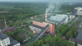 Παλαιά βιομηχανικά κτήρια τούβλου με τον ψηλό σωρό καπνοδόχων που περιβάλλεται από τη δασική εναέρια άποψη άνωθεν φιλμ μικρού μήκους