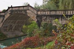 Παλαιά γέφυρα για πεζούς πετρών πέρα από τον κολπίσκο το φθινόπωρο με τα χρώματα φθινοπώρου Στοκ φωτογραφία με δικαίωμα ελεύθερης χρήσης