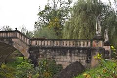 Παλαιά γέφυρα για πεζούς πετρών πέρα από τον κολπίσκο το φθινόπωρο με τα χρώματα φθινοπώρου Στοκ Εικόνες