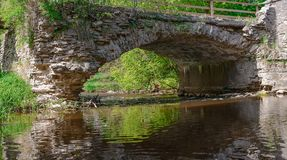 Παλαιά γέφυρα πετρών πέρα από το μικρό ρεύμα στα ξύλα Στοκ εικόνα με δικαίωμα ελεύθερης χρήσης