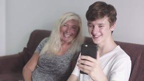 Παλαιά γιαγιά και ενήλικος εγγονός που χρησιμοποιούν την κινητή εφαρμογή στην τηλεφωνική tougether διάταξη θέσεων στον καναπέ Να  φιλμ μικρού μήκους