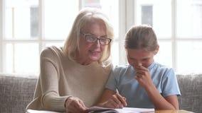 Παλαιά γιαγιά που βοηθά το κορίτσι παιδιών σχολείου εγγονών με την εργασία απόθεμα βίντεο
