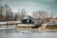 Παλαιά ειδυλλιακά σπίτια στο μικρό αναδρομικό χωριό κοντά στη μικρή παγωμένη λίμνη στοκ εικόνες