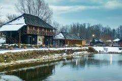 Παλαιά ειδυλλιακά σπίτια στο μικρό αναδρομικό χωριό κοντά στη μικρή παγωμένη λίμνη στοκ φωτογραφίες με δικαίωμα ελεύθερης χρήσης
