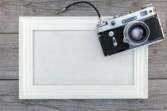 Παλαιά εκλεκτής ποιότητας κάμερα και άσπρο κενό πλαίσιο στο ξύλινο υπόβαθρο Στοκ Φωτογραφίες