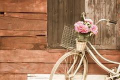 Παλαιά εκλεκτής ποιότητας λουλούδια ποδηλάτων σε ένα καλάθι Σταθμευμένος sidewall του ξύλινου ιδανικού σπιτιών για το κλασικό ύφο στοκ φωτογραφίες με δικαίωμα ελεύθερης χρήσης