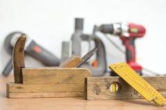 Παλαιά εργαλεία ξυλουργικής στο πρώτο πλάνο Νέα εργαλεία δύναμης στο υπόβαθρο Στοκ Εικόνες