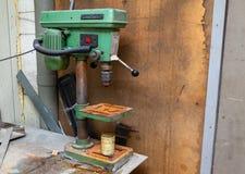 Παλαιά κάθετη πράσινη μηχανή διατρήσεων με ένα μεγάλο κόκκινο κουμπί δύναμης και σκουριά στα στοιχεία σιδήρου σε ένα εργαστήριο β στοκ εικόνα