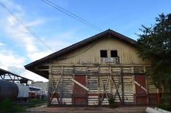 Παλαιά κίτρινη ξύλινη σιταποθήκη με τις κόκκινες ξύλινες πόρτες που έκλεισαν με το πέρασμα του ξύλου στοκ εικόνα