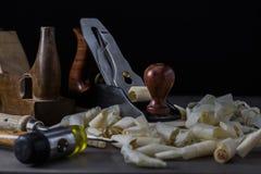 Παλαιά και νέα εργαλεία ξυλουργικής σε μια σκοτεινή ευμετάβλητη ρύθμιση στοκ εικόνες