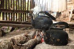 Παλαιά κατσαρόλα στη σόμπα ξυλάνθρακα Στοκ Φωτογραφία