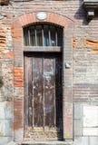 Παλαιά καφετιά στενή ψηλή ξύλινη πόρτα rustick στο ιστορικό σπίτι στο Τ Στοκ εικόνες με δικαίωμα ελεύθερης χρήσης