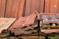 Παλαιά κεραμικά κεραμίδια στεγών που εγκαταλείπονται στο σωρό και που καλύπτονται με τη φόρμα Στοκ εικόνα με δικαίωμα ελεύθερης χρήσης
