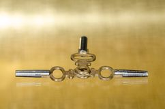 Παλαιά κλειδιά ρολογιών τσεπών ορείχαλκου που βάζουν στη χρυσή επιφάνεια Στοκ Φωτογραφίες