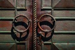 Παλαιά λαβή πορτών στη σκοτεινή πόρτα σιδήρου με τα σφυρηλατημένα προϊόντα, έννοια των αυθεντικών αντικειμένων στοκ φωτογραφία με δικαίωμα ελεύθερης χρήσης